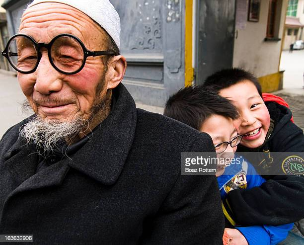 With their grandfather. Photo taken along the silk road in Gansu, China.