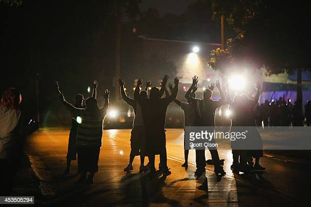 With their hands raised, residents gather at a police line as the neighborhood is locked down following skirmishes on August 11, 2014 in Ferguson,...