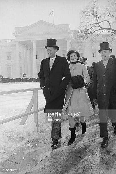 With their new home the White House in background President John F Kennedy and the First Lady walk on a platform to a reviewing stand to watch the...
