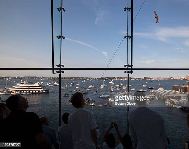With thousands of people gathered at Fan Pier and Boston Harbor a diver jumps from the platform built onto the Institute of Contemporary Art during...