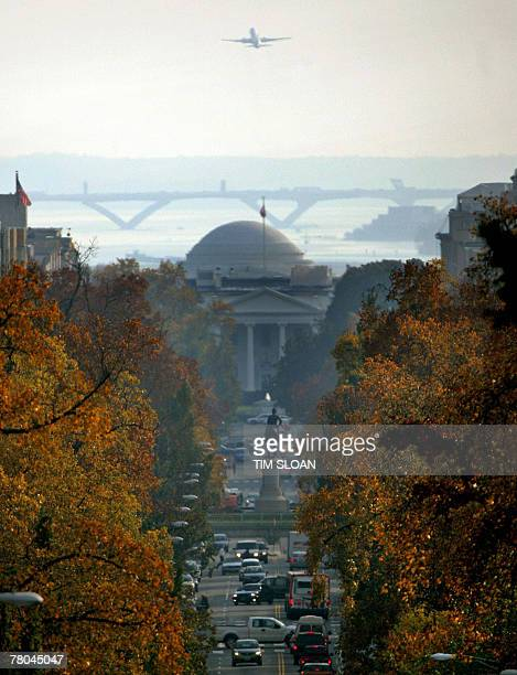 With traffic moving along 16th Street, the dome of the Jefferson Memorial crops above the North Portico of the White House as a commercial jet flies...