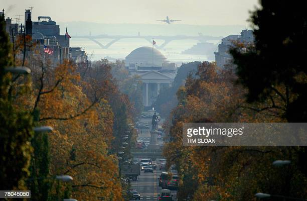 With traffic moving along 16th Street the dome of the Jefferson Memorial crops above the North Portico of the White House as a commercial jet flies...