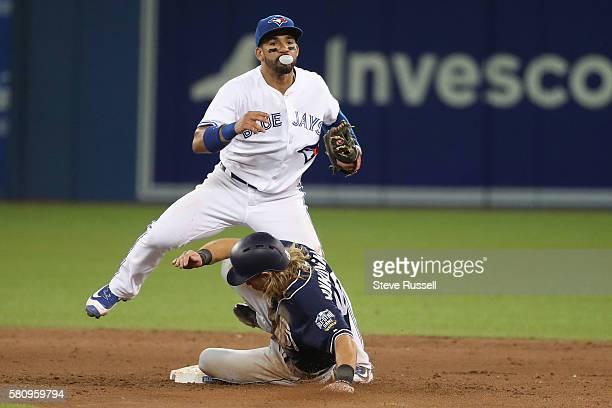 With Travis Jankowski sliding in Toronto Blue Jays second baseman Devon Travis turns the double play in the eighth inning as the Toronto Blue Jays...