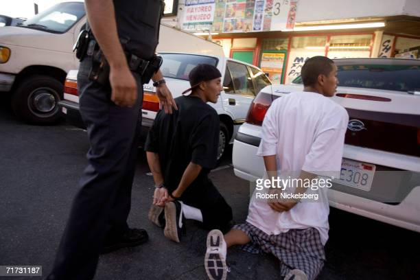 With two 18th Street gang members detained a Los Angeles police gang officer right chases a third member of the gang into a nearby shop on August 4...