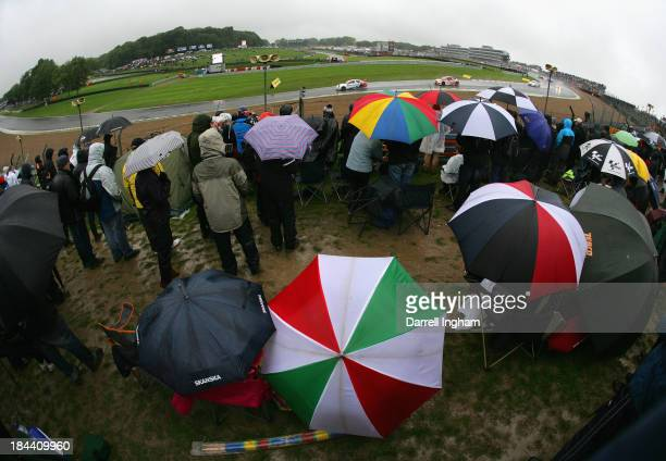 With umbrellas up to protect them from the rain spectators watch from Paddock Hill Bend as Jason Plato driving the MG KX Momentum Racing MG6 leads...