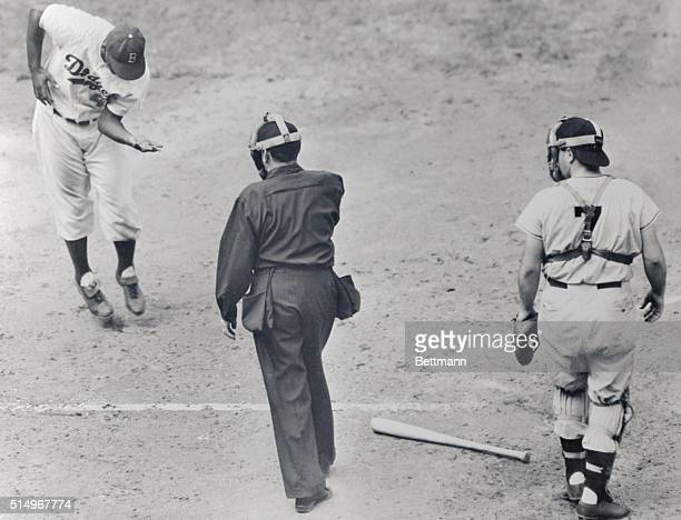 With umpire Ballanfant and Giant catcher Yvars looking on Jackie Robinson of the Brooklyn Dodgers is shown jumping in the air from the intense pain...