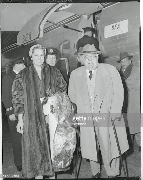 With unconcerned smiles, the Agha Khan III and his beautiful Beghum walk from a Bea Airliner which brought them to the Eternal City with one of its...