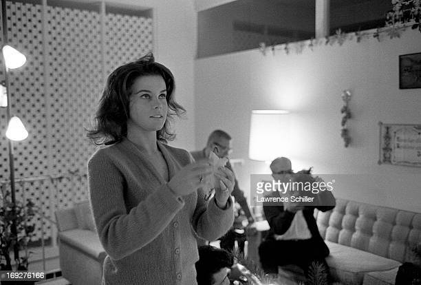With unidentified guests behind her Swedishborn American actress AnnMargret hangs a decoration in her home Los Angeles California 1963