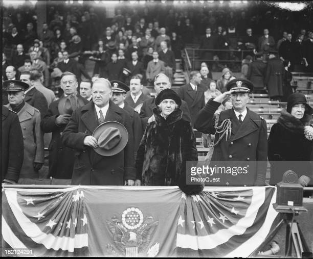 With unidentified others, American politician US President Herbert Hoover and his wife, First Lady Lou Henry Hoover , stand at attention on a...