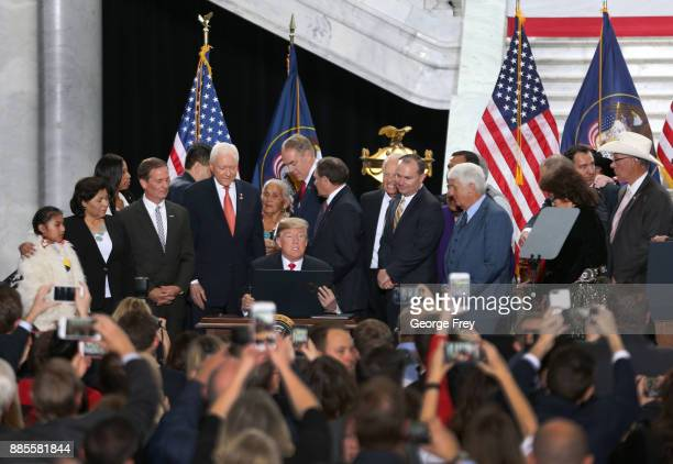 With Utah officials surrounding him US President Donald Trump reads an executive order he signed reducing the Bears Ears National Monument at the...