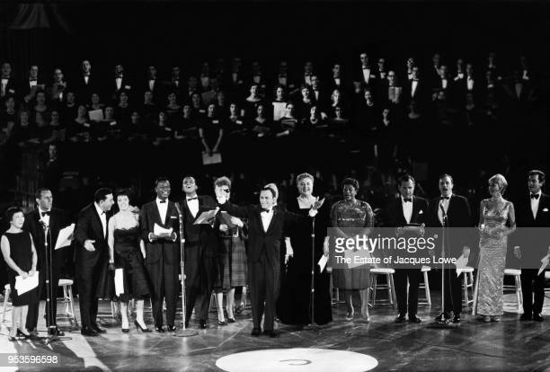 With various celebrities behind him American entertainer Frank Sinatra raises his arms as they all perform during an Inaugural Galam in honor of John...