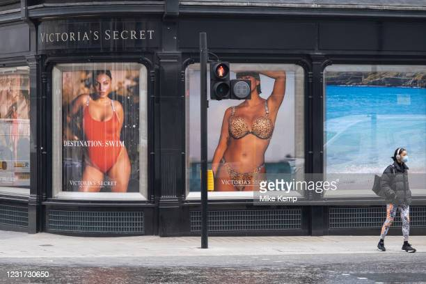 With very few people out and about a figure on Bond Street interacts with large scale advertising pictures outside Victoria's Secret lingerie store...