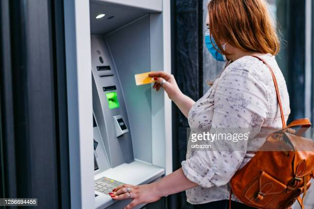 withdrawing money at the atm with face mask on - ginger banks stock pictures, royalty-free photos & images