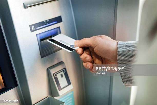 geld abheben von geschäftsmann aus geld am geldautomaten - geldautomat stock-fotos und bilder