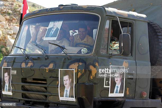 A withdrawing Syrian intelligence vehicle brandishing pictures of president Bashar Assad and loaded with agents and troops head to Syria through the...