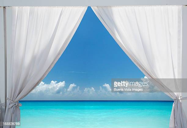 Withe curtains opening over a blue sea