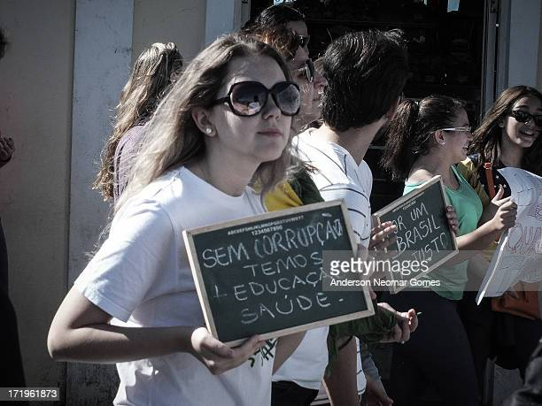 CONTENT] Without corruption we have education and health wrote in the slate a young girl protesting in Brazil marching in city of São Francisco do...
