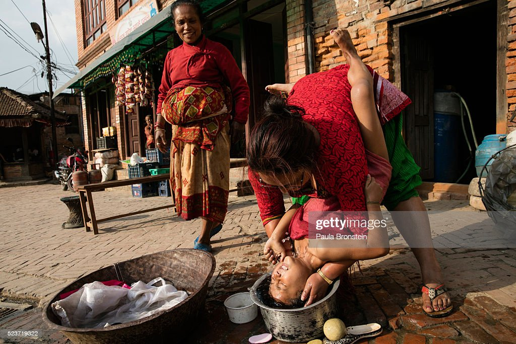 Without running water a mother washes her daughter's hair outside in Bhaktapur on April 23, 2016 in Kathmandu, Nepal. The 7.8-magnitude earthquake struck Nepal close to midday on April 25 last year, killing an estimated 9,000 people. Reports suggest the government promised 2,000USD to affected households but has only paid out a fraction of the amount so far and an estimated 660,000 families are still living in sub-standard temporary shelter or unsafe accommodations one year later.