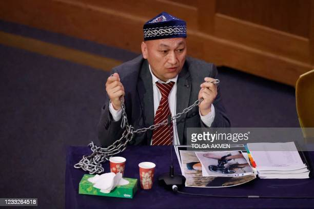 Witness Kazakh-Uyghur Omir Bekali demonstrates how he says he was shackled in chains at a re-education camp as he speaks on the first day of hearings...