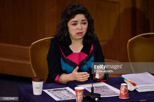 """Witness Uyghur Muslim teacher Qelbinur Sidik reacts as she speaks on the first day of hearings at the """"Uyghur Tribunal"""", a panel of UK-based lawyers..."""