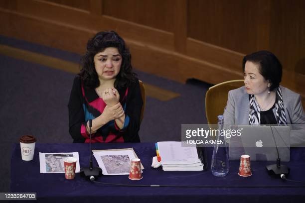"""Witness Uyghur teacher Qelbinur Sidik gestures as she speaks on the first day of hearings at the """"Uyghur Tribunal"""", a panel of UK-based lawyers and..."""