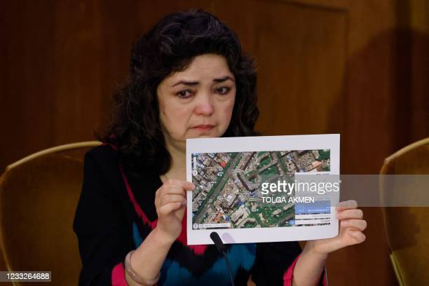 Witness Uyghur teacher Qelbinur Sidik holds up a photograph of the hospital where she says she underwent a forced sterilization procedure on the...