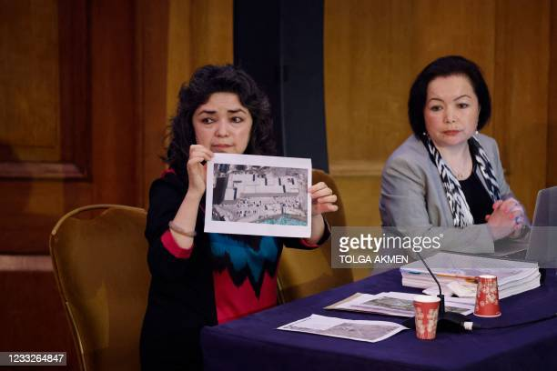 Witness Uyghur teacher Qelbinur Sidik holds up a photograph of what she says is a female-only re-education camp at which she was directed to teach as...