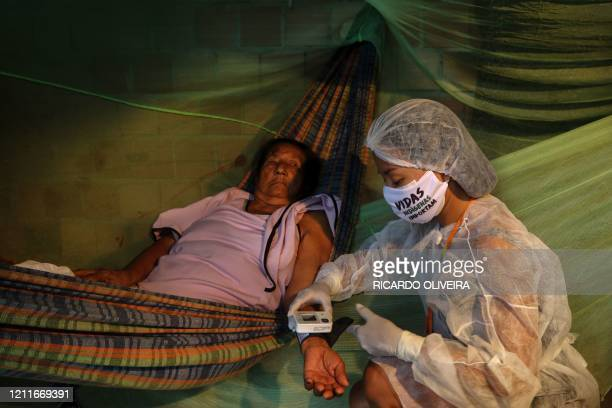 TOPSHOT Witoto indigenous nursing assistant Vanda Ortega takes care of a patient during a healthcare visit in the Parque das Tribos an indigenous...