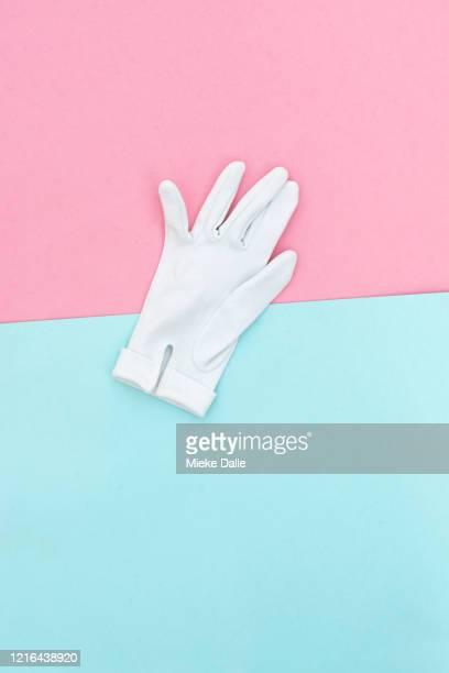 witte handschoen op gekleurde achtergrond - gekleurde achtergrond stock pictures, royalty-free photos & images