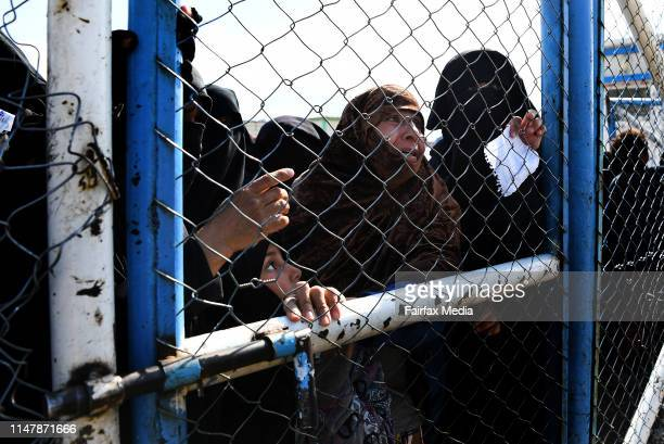 Wives and childern of former ISIS fighters gather at the fence in the foreign section of the al-Hawl refugee camp in northern Syria, close to the...