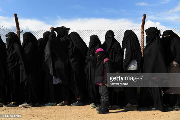 Wives and childern of former ISIS fighters line up in the foreign section of the alHawl refugee camp in northern Syria waiting to be taken to the...