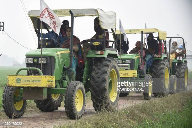 Wives and daughters of farmers practice driving tractors to take part in Women Tractor Rally on the occasion of Republic Day in India's capital Delhi...