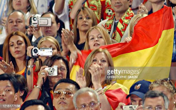 Wives and friends of the Spanish players take photos and wave the country's flag at the start of their second round match against Ireland at the 2002...