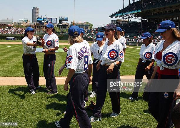 Wives of Chicago Cubs players celebrate winning a charity softball game against the wives of Chicago White players before a game between the Cubs and...