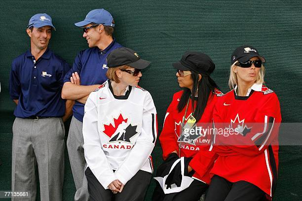 Wives of International Team players chat while Rory Sabbatini and Nick O'Hern of the International Team chat during the final round of competition...