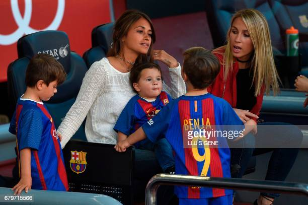 Wives of of Barcelona's Argentinian forward Lionel Messi and Uruguayan forward Luis Suarez Antonella Roccuzzo and Sofia Balbi sit with their children...