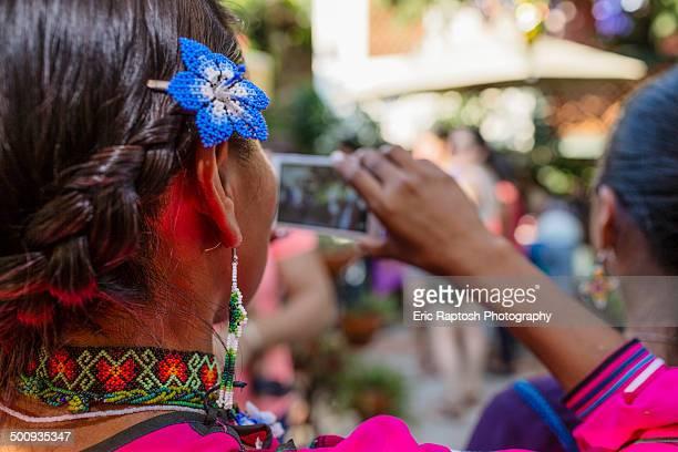Wixaritari woman using cell phone