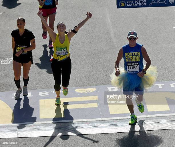 Wk Munsey right crosses the finish line wearing a blue and yellow tutu and Boston Strong tshirt at the 118th Boston Marathon on Monday April 21 2014