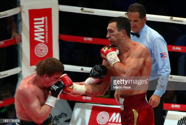Wladimir Klitschko of Ukraine exchanges punches with Alexander Povetkin of Russia during their WBO WBA IBF and IBO heavy weight title fight between...