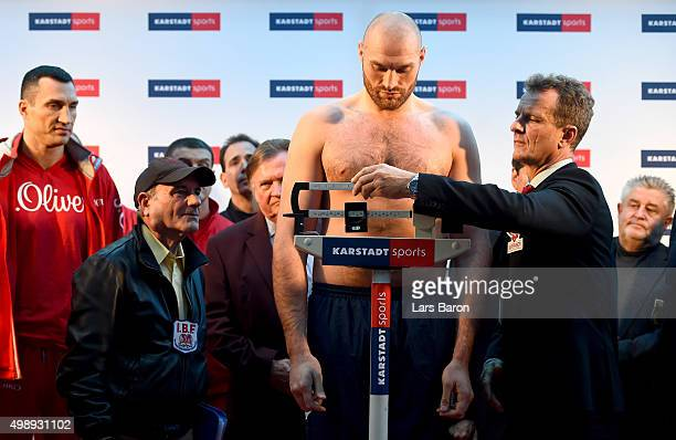 Wladimir Klitschko of Ukraine looks on as his challenger Tyson Fury of UK stands on the scales during the weigh in at Karstadt Sport on November 27,...