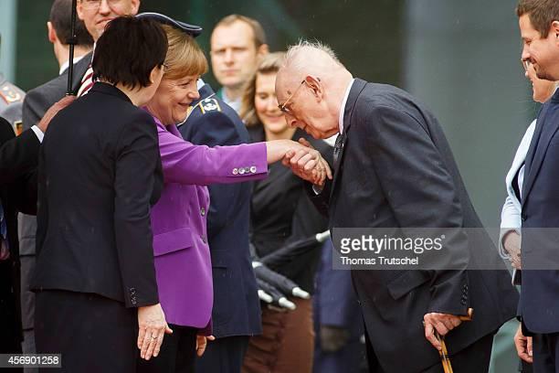 Wladyslaw Bartozewski former Polish Foreign Minister kisses the hand of German Chancellor Angela Merkel at Chancellery during a visit of Polish Prime...