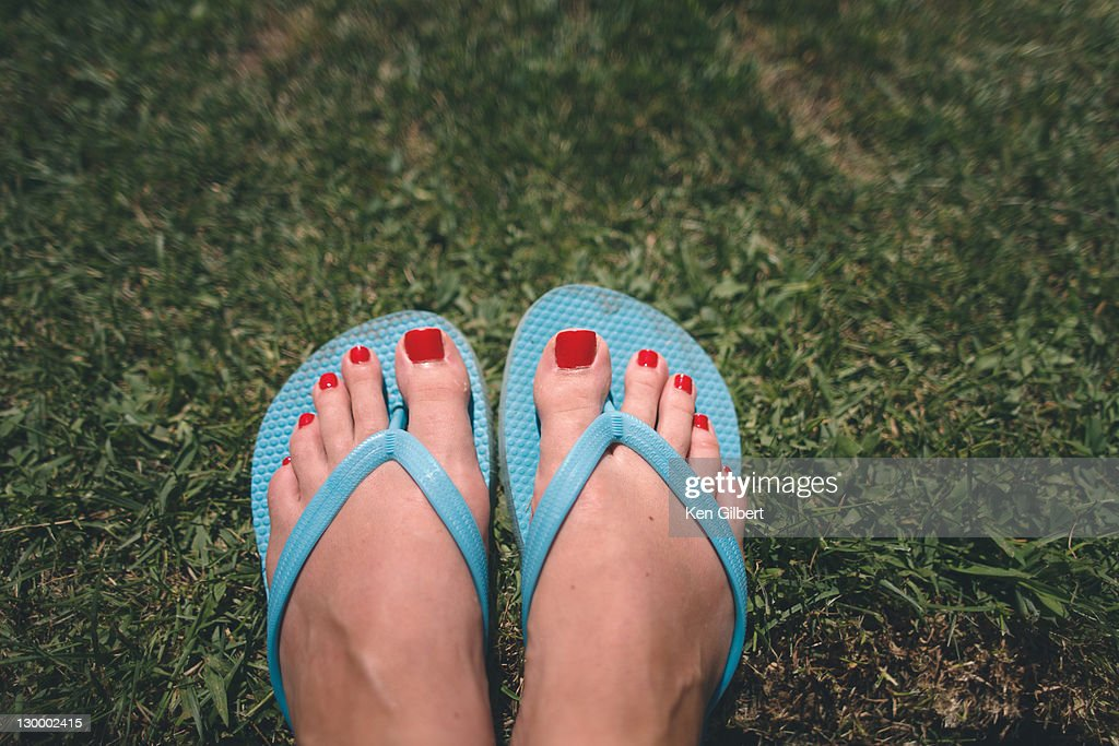 Wman's pedicured feet in flipflops rest on grass : Stock Photo