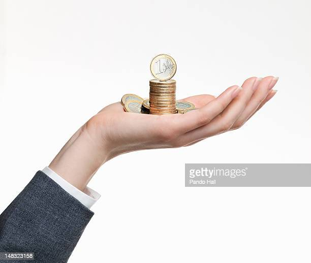 Wmaon holding a stack of euro coins in her hand