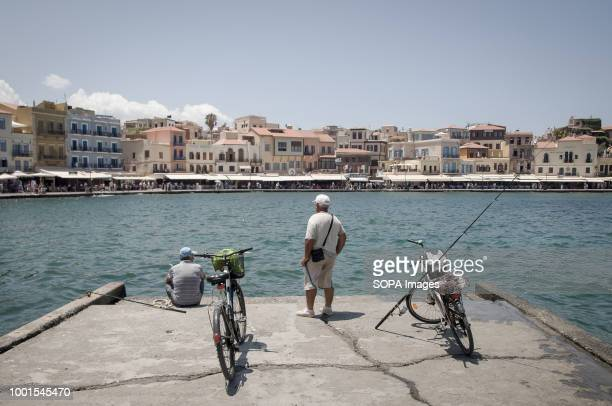 wo fishermen seen fishing at the old port of Chania Chania is a very touristic place in Crete where tourists come to enjoy the Chania lighthouse and...