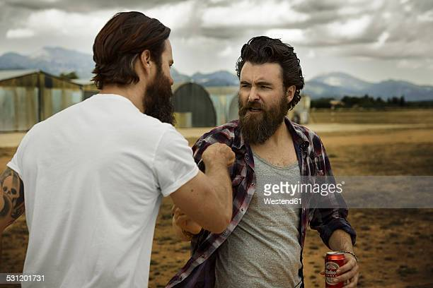 wo men with full beards fighting in abandoned landscape - 勝負 ストックフォトと画像