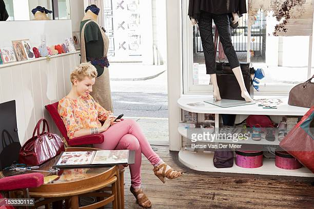 woamn looking at mobile phone in fashion shop. - one young woman only stock pictures, royalty-free photos & images