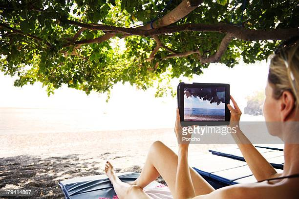 woamn making a photo with an iPad at the beach