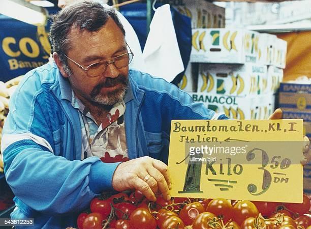 Ein Markthändler steckt ein Preisschild zwischen seine Auslage von Baumtomaten aus Italien Im Hintergrund Bananenkartons Aufgenommen 1994