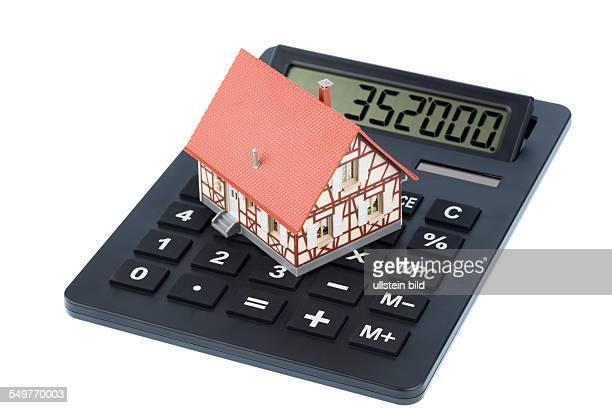 Wohnhaus auf einem Taschenrechner Symbolfoto für Hauskauf Kosten und Sparen