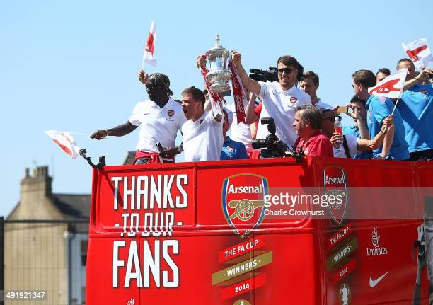 Wojciech Szczesny and Aaron Ramsey of Arsenal lift the FA cup during the Arsenal FA Cup Victory Parade on May 18 2014 in London England